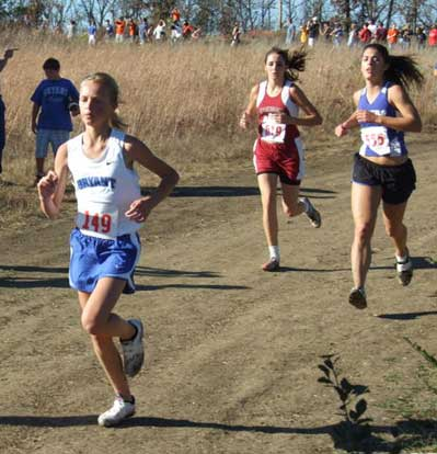 Ashlyn Lessenberry, left, keeps pace ahead of a pair of competing runners during Saturday's State cross country meet at Mountain Home.
