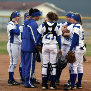 Bryant head coach Lisa Stanfield meets with her infield during a break in Monday's game.