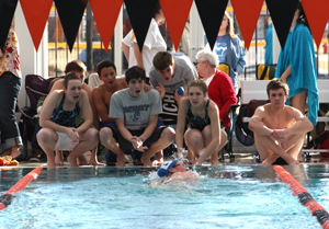 Members of the Bryant High School swim team cheer on teammate Jordan Martin in the 500 yard freestyle at a recent meet at Hendrix.