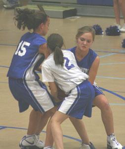 Shelby Gartrell (15) and McKenzie Rice, right, battle Bethel's Lisa Walker for possession.