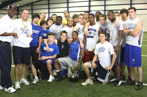 Bryant head football coach Paul Calley accepts the $1000 donation after this group of Hornets out-performed a contingent of Benton players in a scouting combine-styled event at D1 Sports Training in Little Rock.