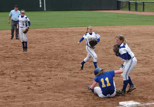 Bryant's Jessie Taylor (9), Kim Wilson (2) and Christen Kirchner (right) react after catching North Little Rock's Allie Seaton (11) in a rundown during Saturday's State championship game. (Photo by Mark Hart)
