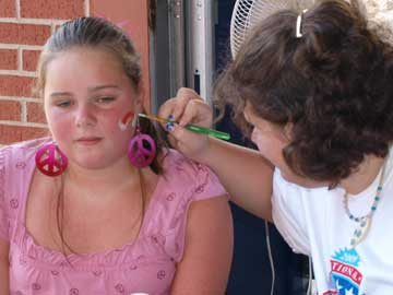 Sara Scroggins gets her face painted by Kate Coffman. (Photo by Lana Clifton)