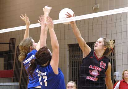 Peyton Thacker and Sydney Manley attempt a block in the Bryant JV contest Tuesday. (Photo by Mark Hart)