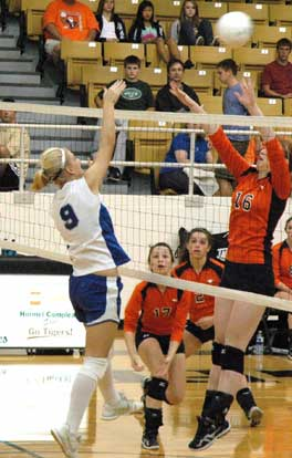 Maggie Hart (9) sends a hit over the block attempt of a pair of Heritage players. (Photo by Mark Hart)