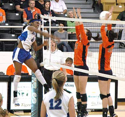 Bryant's Breanna White, left, recoils after going high for a spike on Tuesday. (Photo by Mark Hart)