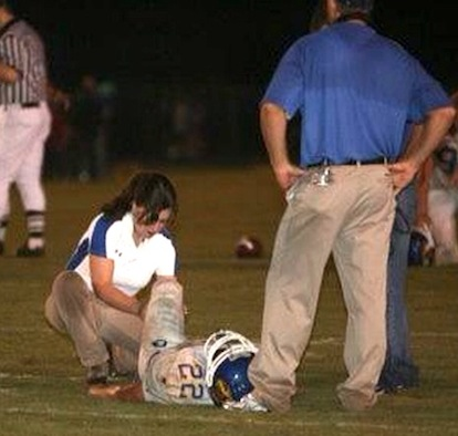 Athletic trainer Krista Finney tends to a Sheridan player during the Bryant-Sheridan football game in 2008. (photo by Rick Nation)
