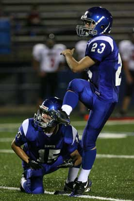 Davis Nossaman kicks an extra points out of the hold of Jacob Irby. (Photo by Rick Nation)