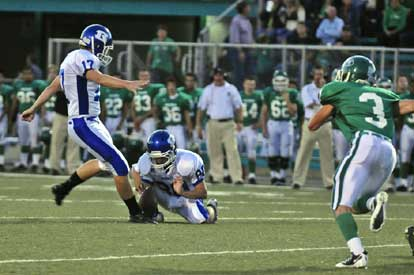 Jace Denker kicks one of his field goals out of the hold of Tyler Jamison as Van Buren's Anthony Gibbons (3) puts on the rush. (Photo by Ron Boyd)