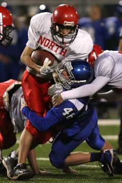 Kyle Lovelace (46) fights off a hold to make a tackle. (Photo by Rick Nation)
