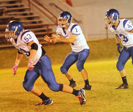 Ty Harris sets to receive a snap as Ryan Hall (53) and Brent Reeves (43) get started on the play. (Photo by Kevin Nagle)