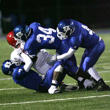 Aaron Bell (7), Walter Dunn (34) and Jesse Johnson (4) make a tackle. (Photo by Rick Nation)