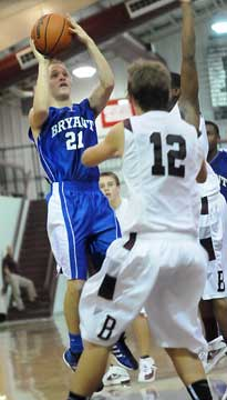 John Winn (21) pulls up in the lane for a jumper over Benton's Braden Warhurst (12). (Photo by Kevin Nagle)