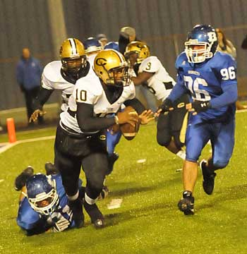 Tim Kelly (on ground) trips up Central quarterback Cammreon Polite (10) as teammate Austin Dunnahoo arrives to help out. (Photo by Kevin Nagle)