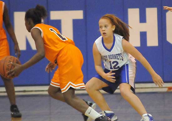 Bryant Blue's Kara Moser (12) defends a Ridge Road ballhandler during Thursday's game. (Photo by Kevin Nagle)