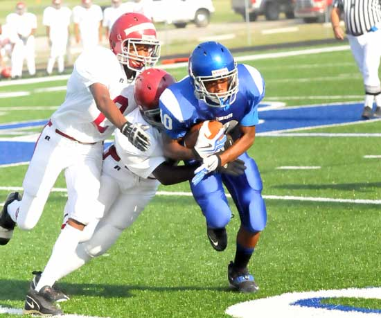 Steven Murdock is dragged down by a pair of Pine Bluff players after catching a pass. (photo by Kevin Nagle)