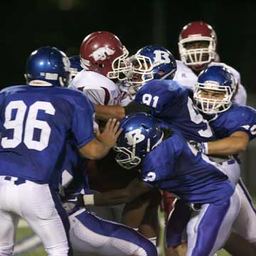 Tim Kelly (91), Dillon Winfrey (2), Austin Dunahoo (96) and others pile up a Texarkana ballcarrier. (Photo by Rick Nation)