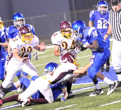 Travon Lee (18) tries to find some running room. (Photo by Kevin Nagle)