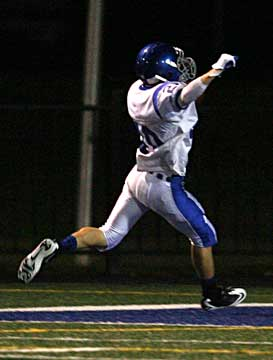 Bryant's Drew Tipton raises his arms as he scores on an interception return. (Photo by Rick Nation)