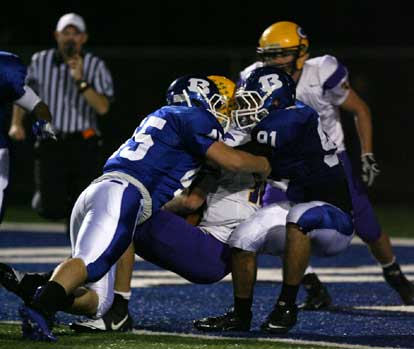 Michael Smith (95) and Tim Kelly (91) make a bid to bring down Catholic's Zach Conque for a safety. (Photo by Rick Nation)