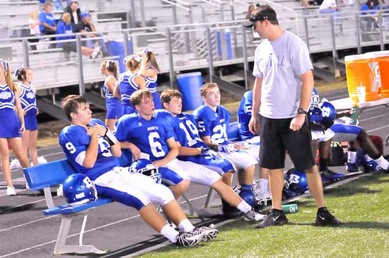 Coach Jason Hay visits with Wesley Akers (9), Austin Powell (6), Jacob Irby (19) and Austin Vail (25). (Photo by Kevin Nagle)