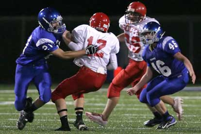 Ben Bruick (21) pulls down Cabot South quarterback Jonathan Gilleylan as Kyle Lovelace (46) arrives to help. (Photo by Rick Nation)