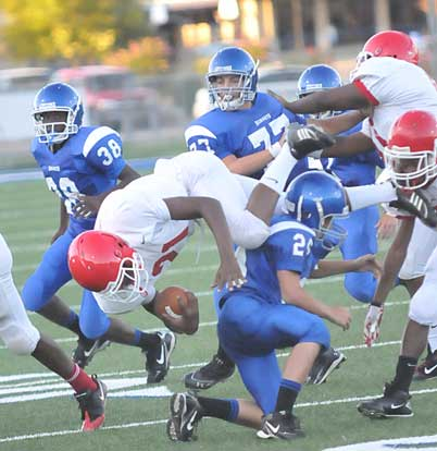 Houston Chavis makes a tackle as Jordan McDonald (38) and Gavin Haas (77) look to get in on the play. (photo by Kevin Nagle)