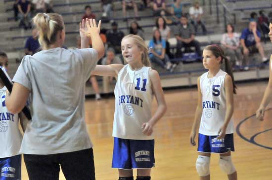 Bryant White coach DeAnna Ward gives Reagan Blend a high five during a break in Tuesday's action as Breanna Hall (5) follows to the bench. (Photo by Kevin Nagle)
