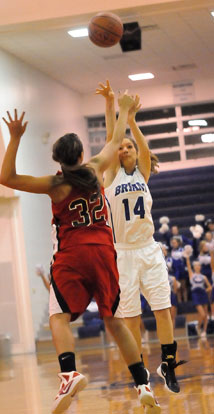 Peyton Weaver (14) tries to shoot over Russellville's Kaylee Weidower. (Photo by Kevin Nagle)