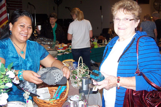 From left, Maria Evans, a vendor at the Bryant Senior Center Market Day, assists customer Guyva Thomas of Bryant with items for sale. Proceeds from Market Day benefitted the Bryant Senior Center meals for seniors program.