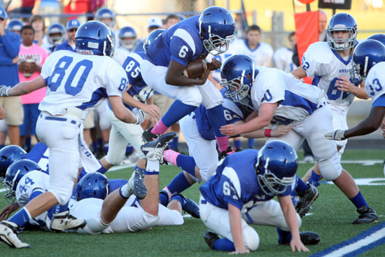 Bryant Blue running back Phillip Isom-Green leaps over the pile to try to pick up extra yardage. (Photo by Rick Nation)