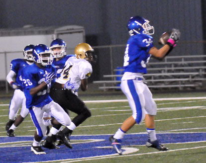 Devon Alpe (34) makes an interception as Kris Croom (26) looks for someone to block. (Photo by Kevin Nagle)