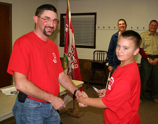 Colton Ellis receives his Scout badge.