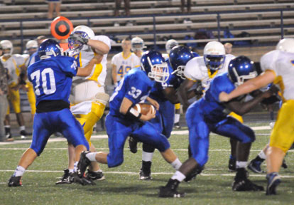Drew Alpe (33) cuts behind blocks from Zach Jackson (70), Cameron Murray and Demaja Price (right). (Photo by Kevin Nagle)