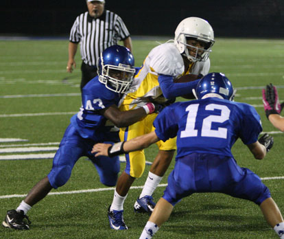 Khaliq Slater (43) grabs on and Evan Lee (12) prepares to help out. (Photo by Rick Nation)