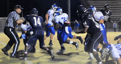 Hornets senior Tyree Reese (33) crashes towards the end zone off a block by Jacob Ward (50) and others. (Photo by Kevin Nagle)