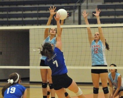 Courtney Davidson (7) attacks against a pair of Lady Rebels. (Photo by Kevin Nagle)