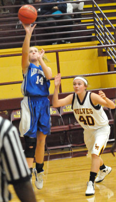 Riley Hill (14) launches a shot from the baseline as Skylar Foster defends. (Photo by Kevin Nagle)