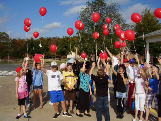 Third grade students release red balloons.