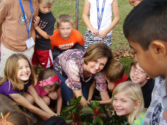 Second grader students help plant flowers and shrubs.