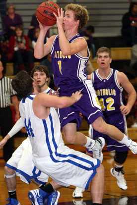 Bryant's Zach Cambron, left, takes a charge, one of three on the night, as Catholic's Sam Greenwood drives to the basket. (Photo by Rick Nation)