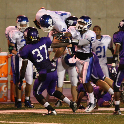 Bryant's Nate Rutherford (88) goes airborne to pick up extra yardage as K.J. Hill blocks. (Photo by Rick Nation)