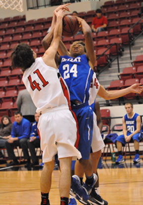Jaylen Peterson (24) gets a shot blocked in front and a slap on the head from behind. (Photo by Kevin Nagle)
