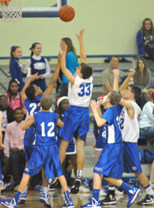 Brooks Ellis puts up a shot over Bryant Blue's Brandon Shirlee (23) and Sam Chumley (12). (Photo by Kevin Nagle)