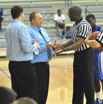 Bryant White coach Heath Long, left, and Bryant Blue coach Derek McGrew discuss a scorebook discrepency with one of the officials Monday night. (Photo by Kevin Nagle)