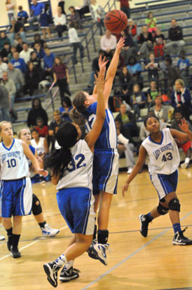 Bryant Blue's Sarah Kennedy (12) releases a shot in front of Bryant White's Kennedy Harris (32) and Deja Rayford (43). (Photo by Kevin Nagle)