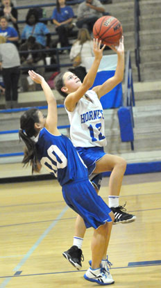 Maddie Stephens (12) goes up for a shot as Cadie Anderson defends. (Photo by Kevin Nagle)