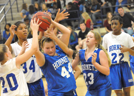 Bryant Blue's Stephanie Cullen (44) secures a rebound in a crowd including teammate BAylee Rowton and Bryant White's Maddie Miller (20), Raven Loveless (34) and Jaylen Sparks (22) during Monday night's game. (Photo by Kevin Nagle)