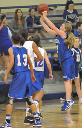 Bryant Blue's Baylee Rowton launches a shot in front of teammate Raija Todd (13) and Bryant White's Raven Loveless and Maddie Stephens (12). (Photo by Kevin Nagle)
