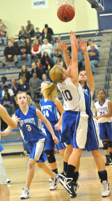 Bryant White's Lauren Lessenberry (10) puts up a shot over Bryant's Blue's Sarah Kennedy and Bethany Hutchison (3). (Photo by Kevin Nagle)